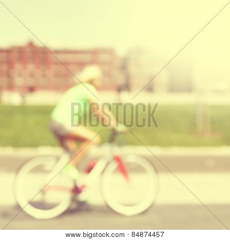 Abstract blurred image of woman on bicycle in the city.