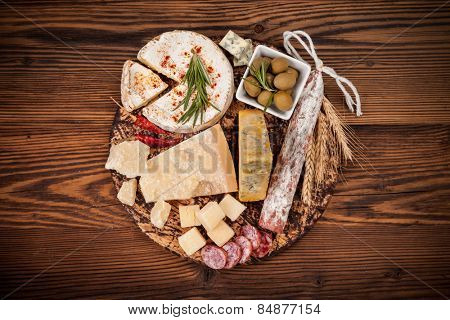 Cheese arrangement served on cutting board. Shot from aerial view