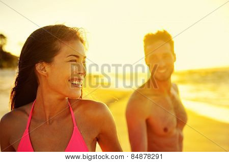 Happy multicultural couple on beach vacations. Hawaii in sunset, young healthy adults together laughing walking in summer day. Asian mixed race woman, Caucasian man.