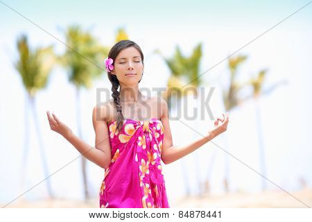 Happy Asian woman meditating on Hawaiian palm beach in sarong, hands up. Beautiful mixed race female model enjoying sun in worship and meditation zen. Big Island, Hawaii, USA.