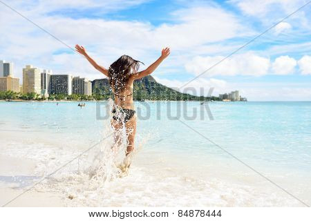 Waikiki beach fun - happy woman on Hawaii vacation. Unrecognizable young adult from behind jumping of joy in water waves, arms up with diamond head mountain in the background, landmark of Honolulu.