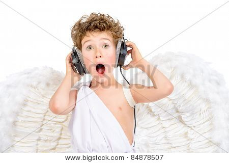 Happy little boy in a costume of angel listening to music in headphones. Cupid. Valentine's day.