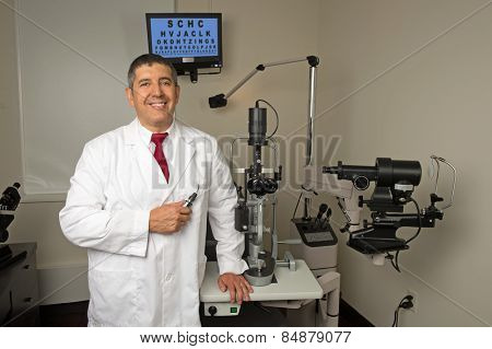 Hispanic eye doctor in examination room surrounded by testing machines