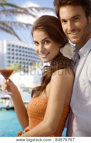 Young happy casual caucasian couple with cocktail drink at luxury summer beach holiday resort. Standing, smiling, looking at camera.