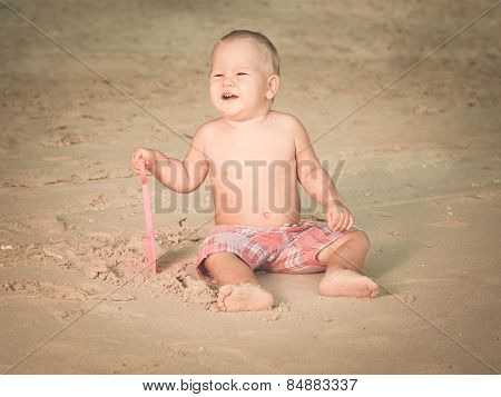 Cute baby on the tropical beach playing toys. Toned