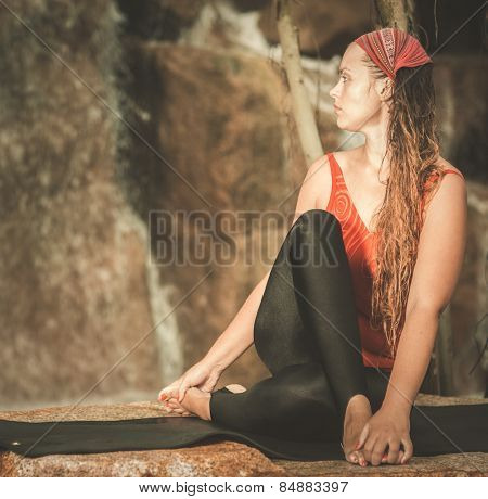 Woman practicing yoga near waterfall. Half Spinal Twist Pose. Ardha Matsyendrasana. Toned