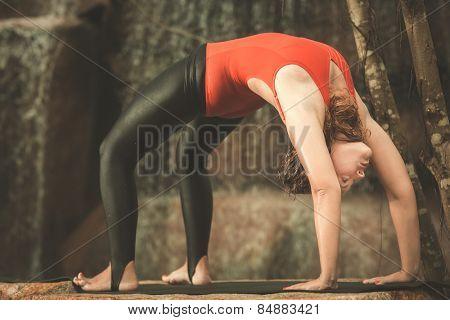 Woman practicing yoga near waterfall. Wheel Pose. Chakrasana. Toned