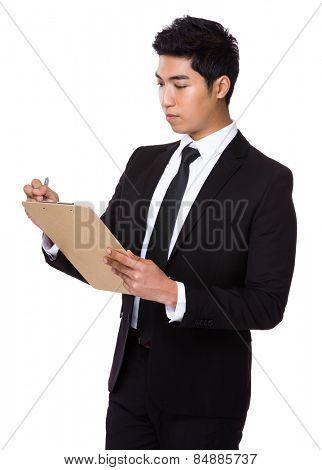 Businessman write on clipboard