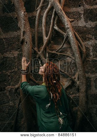 Rear View of Stylish Young Woman in Green Shirt with Dreadlocks Touching Tree Roots on the Wall.