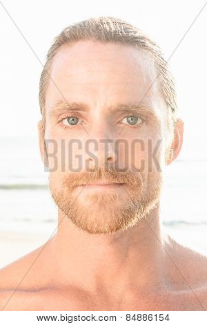 Handsome blond man with bare shoulders and a beard gazing directly at the camera on a high key beach background with flare from summer sunshine