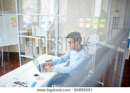Young man typing by desk in office