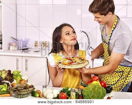 Young happy family cooking pizza at kitchen. Woman looking man.