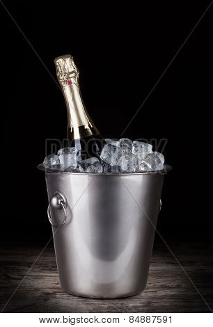 Champagne bottle in a bucket with ice on the dark background