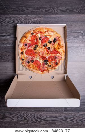 Top view of Italian pizza with ham, tomatoes, and olives in box, on gray table background