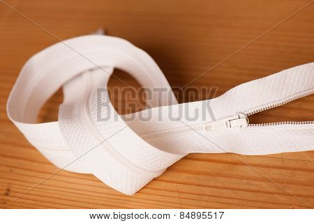 White Zipper On A Wooden Background
