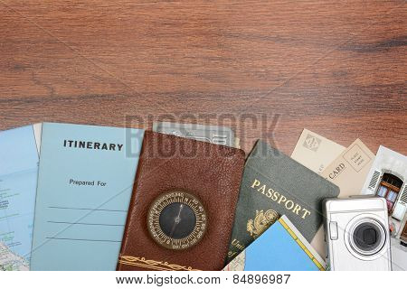 High angle shot of a travel still life. Items include: passport, wallet, post cards, camera, pictures, maps, and itinerary folder on a wood desk. Horizontal format with copy space at the top.