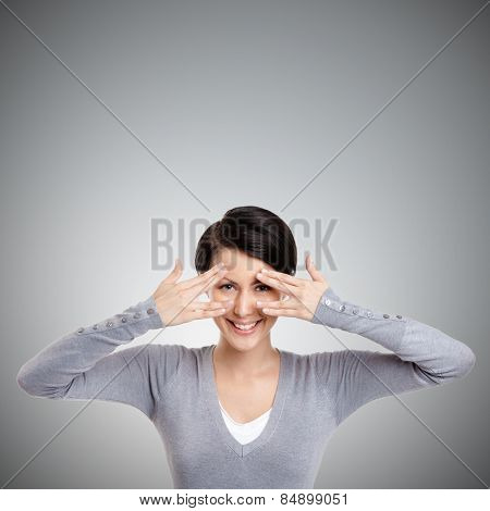 Beautiful young woman covers her eyes with hands, isolated on grey