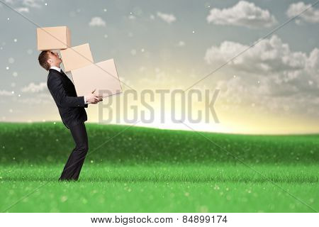 Manager holding pile of pasteboard boxes, nature background