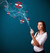 stock photo of smoking woman  - Beautiful young woman smoking dangerous cigarette with no smoking signs - JPG