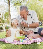 foto of grandfather  - Loving Grandfather and Granddaughter Coloring Easter Eggs Together on Picnic Blanket At The Park - JPG