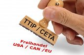 picture of free-trade  - CETA and TTIP Transatlantic trade and investment partnership printed on rubber stamp in hand with text in german language - JPG