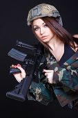 stock photo of assault-rifle  - Woman in the military uniform with an assault rifle on the shoulder over black background - JPG