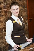 stock photo of receptionist  - smiling female receptionist passing key card to guest - JPG