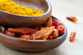 stock photo of curcuma  - Asian spices dried red chili and curcuma in wooden bowls closeup - JPG