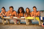 stock photo of sunbathers  - Group of multi ethnic friends sunbathing on a deck chairs on a beach  - JPG