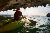 foto of cave woman  - Young lady paddling the kayak from limestone cave towards open sea - JPG