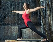 stock photo of virabhadrasana  - Woman practicing yoga near waterfall - JPG