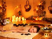 stock photo of black woman spa  - Woman getting stone therapy massage in bamboo spa - JPG