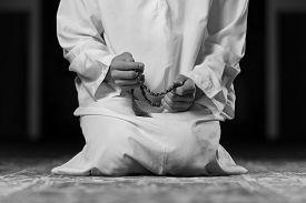 image of muslim man  - Young Muslim Man Making Traditional Prayer To God While Wearing A Traditional Cap Dishdasha - JPG