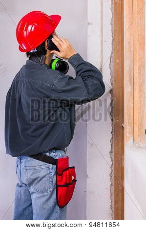 Worker Wearing Hard Hat And Earmuffs While Having A Phone Call
