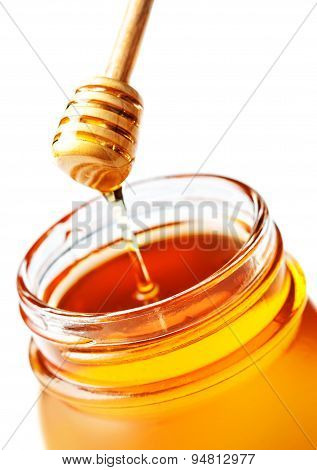 ..honey Dipping With Honey In Glass Jar Isolated On White Background Macro. Wooden Honey Dipper Clos