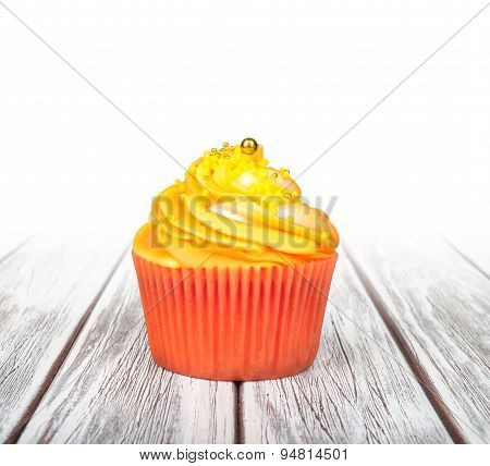 Orange Cupcake With Yellow Cream On White Wooden Background With Isolated Background