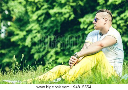 Pretty Young Men In Sunglasses Sitting On The Grass In The Park