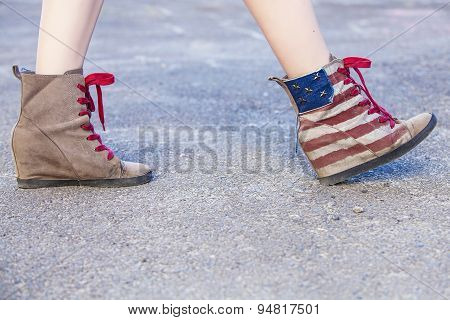 Female Legs In Sneakers With The Design Of The American Flag On The Grass