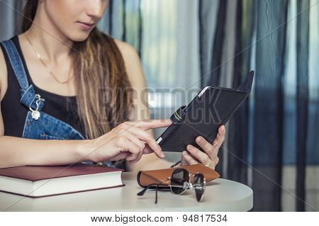 Woman With E-book The Tablet Sits At A Table