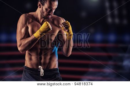Strong Muscular Boxer In Red Boxing Gloves. A Man In A Boxing