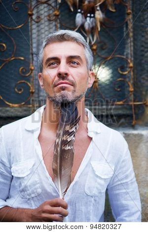 Sexi Man In A White Shirt And Ornamental Window On Background. And Dream Catcher And Eagle Feathers.