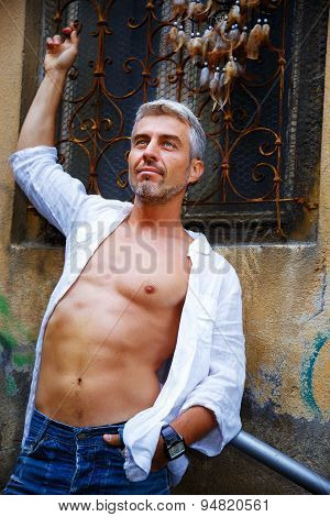 Sexi Man In A White Shirt And Ornamental Window On Background. And Dream Catcher