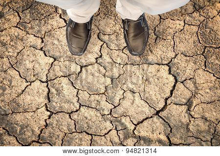 Man Standing On A Dry Cracked Earth