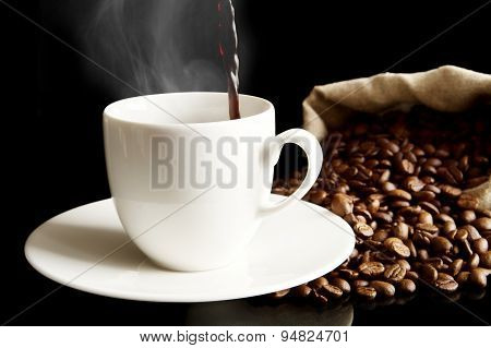 Poured Coffee To Cup With Full Bag Isolated On Black