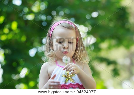 Blonde girl blowing on white Taraxacum officinale or common dandelion seeds