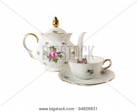 Porcelain teapot, teacup and saucer with floral rose ornament in classic style isolated over white