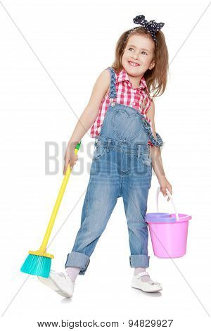 Funny funny little girl in denim overalls holding