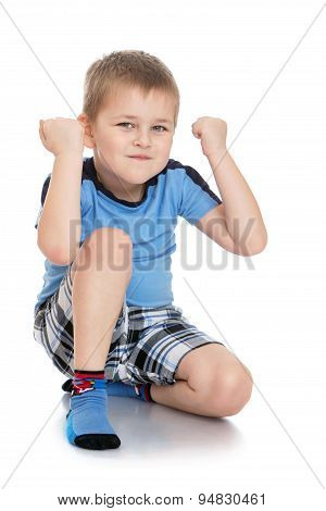 Serious little boy in shorts and blue t-shirt shows the fists