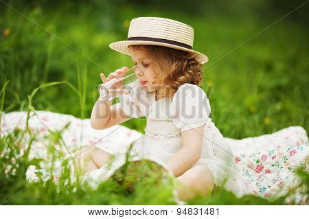 Little Girl Sitting And Drinking