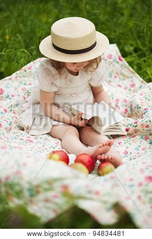Little Girl Sitting And Reading A Book